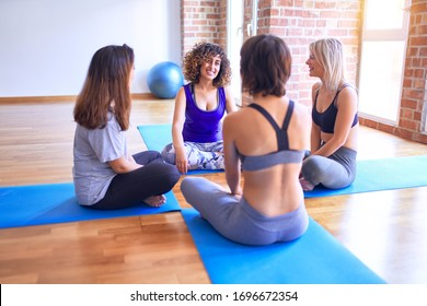 Young beautiful group of sportswomen smiling happy practicing yoga. Sitting on the mat speaking after class at gym