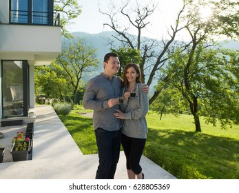 young beautiful handsome couple enjoying morning coffee in front of their luxury home villa