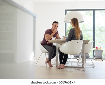 young beautiful handsome couple enjoying morning coffee and strawberries in their luxurious home villa