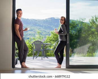 young beautiful handsome couple enjoying morning coffee and breakfast on the door of their luxury home villa