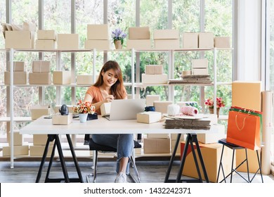 Young beautiful happy asian business woman owner of SME online using laptop receive order from customer with parcel box packaging at her startup home office, online business seller and delivery