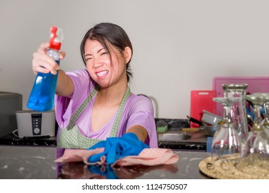 young beautiful and happy Asian Chinese woman cleaning and washing with spray bottle at home kitchen in rubber gloves enjoying domestic chores in cheerful and positive housekeeping