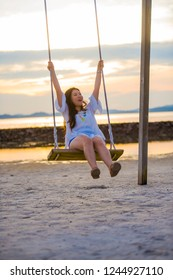 young beautiful and happy Asian Chinese woman enjoying summer holidays trip at beach resort smiling cheerful on swing having fun feeling free and relaxed swinging on sunset at the sea