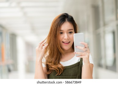 Young beautiful happy Asian girls laugh and smile while having fun with smartphone mobile indoor.