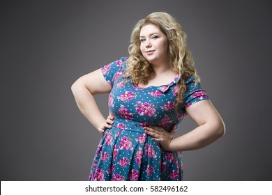 Young beautiful happy blonde plus size model in dres, xxl woman portrait on gray studio background, makeup and hairstyle