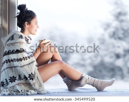 Young beautiful happy brunette woman drinking cup of coffee wearing knitted nordic print poncho sitting home by the window. Blurred winter snow tree background
