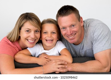 young beautiful and happy Caucasian couple with mother and father posing cheerful together with adorable 7 years old blond little girl in parents and daughter love and lifestyle concept