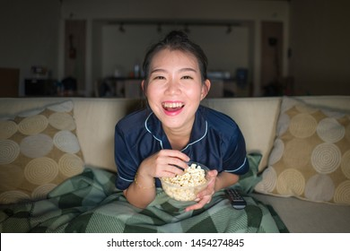 young beautiful happy and cheerful Asian Chinese woman watching television comedy movie or hilarious show laughing and eating popcorn sitting at home couch with blanket in domestic lifestyle