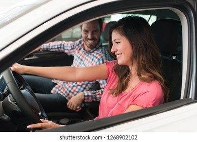 Young beautiful happy couple buying a car. Husband buying car for his wife in a salon. Woman driving a car and smiling. Car shopping concept.