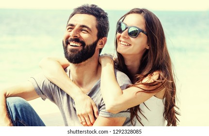 Young beautiful happy couple in love tenderly embracing against the background of the sea, love honeymoon Valentine's Day concept.