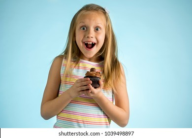 young beautiful happy and excited blond girl 8 or 9 years old holding chocolate cake on her hand looking spastic and cheerful in sugar calories and unhealthy sweet nutrition abuse addiction concept