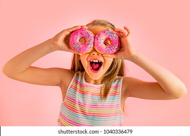 young beautiful happy and excited blond girl 8 or 9 years old holding two donuts on her eyes looking through them playing cheerful in sugar calories and unhealthy sweet nutrition abuse addiction