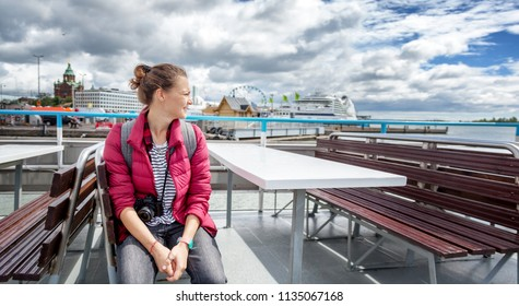 Young beautiful happy girl traveler with a camera in her hands examines the places of Helsinki, the capital of Finland with a pleasure boat. Travel to Scandinavia