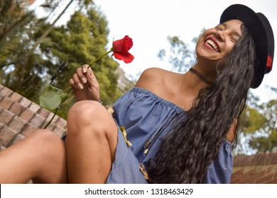 Young, beautiful, happy and in love brunette woman just received a beautiful rose from her suitor, her boyfriend. She wears a blue dress with uncovered shoulders, fedora hat with red feather and loose