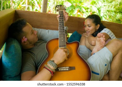 young beautiful and happy mixed ethnicity couple in hipster style chilling outdoors playing guitar relaxed at tranquil garden enjoying holiday retreat together in love and freedom concept