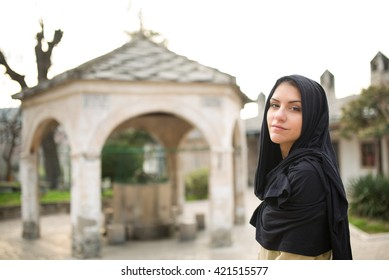 Young beautiful happy Muslim woman outdoors portrait.Gorgeous Muslim woman in front of mosque posing