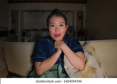 young beautiful happy and relaxed Asian Chinese woman at home living room sitting cozy on sofa couch watching TV show episode or romantic comedy movie smiling sweet and enjoying alone