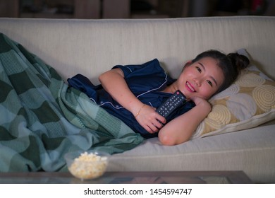 young beautiful happy and relaxed Asian Chinese woman at home living room lying cozy on sofa couch watching TV show episode or romantic comedy movie eating popcorn smiling and having fun