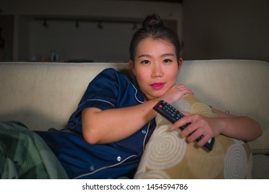 young beautiful happy and relaxed Asian Chinese Korean at home living room lying cozy on sofa couch watching TV show episode or romantic comedy movie smiling sweet and enjoying alone