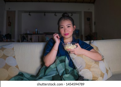 young beautiful happy and relaxed Asian Chinese woman at home living room sitting cozy on sofa couch watching TV show episode or romantic comedy movie eating popcorn smiling and having fun