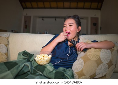 young beautiful happy and relaxed Asian Korean woman at home living room sitting cozy on sofa couch watching TV show episode or romantic comedy movie eating popcorn smiling and having fun