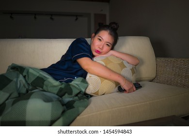 young beautiful happy and relaxed Asian Chinese Japanese at home living room lying cozy on sofa couch watching TV show episode or romantic comedy movie smiling sweet and enjoying alone
