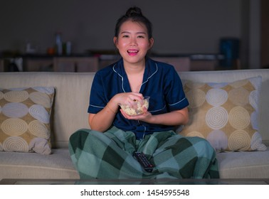 young beautiful happy and relaxed Asian Chinese Korean at home living room sitting cozy on sofa couch watching TV show episode or romantic comedy movie smiling sweet and enjoying alone