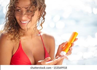 Young beautiful happy smiling cheerful tanned woman with sun-protection cream on beach, during sun bathing