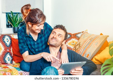 Young beautiful happy smiling couple sitting on the sofa in a cozy home surfing online using a tablet