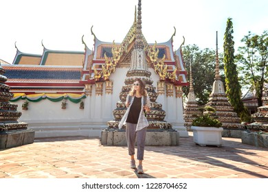 Young beautiful happy smiling european tourist woman in a hat and glasses at a buddhist temple in Bangkok traveling to southeast Asia