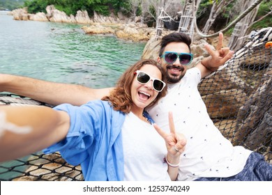 Young beautiful happy smiling funny couple man and woman best friends on a hammock on vacation makes selfie on  smartphone against the background of the sea