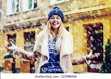 Young beautiful happy smiling girl acting thrilled, wearing stylish clothes. Model expressing joy and excitement with hands and face. Snowfall. Christmas, new year, winter holidays concept. Waist up