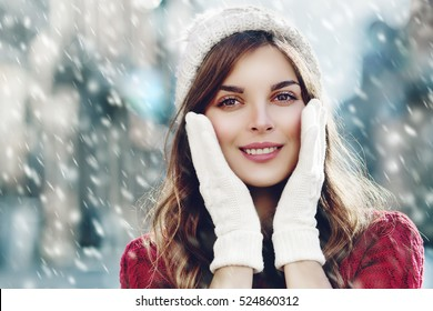 Young beautiful happy smiling girl walking on street. Model looking at camera, touching her face, wearing stylish knitted winter hat and gloves. Close up. Outdoor. Toned. Copy, empty space for text
