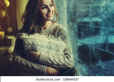 Young beautiful happy smiling girl sitting on the windowsill, holding pillow and looking through window. Night. Christmas, New year, winter holidays concept. Close up. Copy space for text. Toned