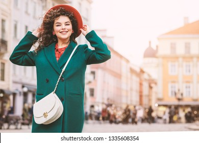 Young beautiful happy smiling lady wearing orange hat, green coat, with white cross body bag posing in street of European city. Copy, empty space for text
