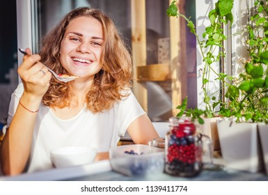 Young beautiful happy smiling woman eating yogurt and fresh berries at breakfast at home