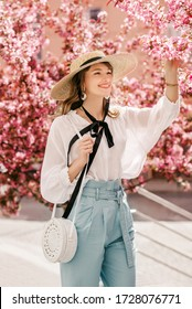 Young beautiful happy smiling woman wearing trendy wide brim straw hat, white vintage blouse, stylish blue high waist trousers with round wicker rotang bag, posing near pink spring blossom trees