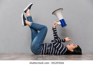 Young beautiful happy smiling woman lying with legs up and speaking in megaphone