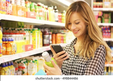 Young beautiful happy smiling woman using mobile in supermarket at natural and biologic juices area. Checking price and ingredients with phone. App shopping concept.