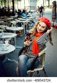 Young beautiful happy stereotypical french girl in a Parisian street cafe