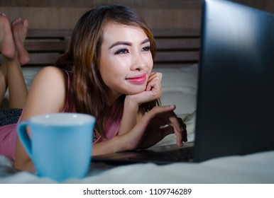 young beautiful and happy student woman enjoying on bed with laptop computer watching internet movie or having video chat call with friend at night  in her bedroom drinking tea cup