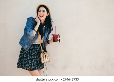 young beautiful happy stylish hipster girl, cocktail, smoozy drink, denim jacket, smiling, fashion, teen, cool accessories, purse, hat, sunglasses, amazed, vintage style, wall background, hair, wind