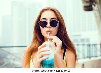 young beautiful happy stylish hipster girl, cocktail, smoozy drink, denim jacket, smiling, fashion, teen, cool accessories, purse, hat, sunglasses, amazed,vintage style outfit,wall background smoothie