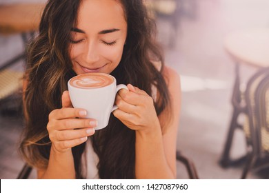 Young beautiful happy woman with long curly hair enjoying cappuccino in a street cafe