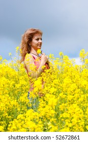 young beautiful happy woman on rapeseed field