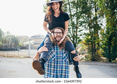 Young beautiful happy woman shoulder riding her bearded boyfriend outdoor throughfare - celebration, good news, happiness concept