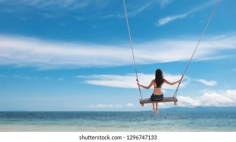 Young beautiful happy woman in top and shorts swinging on a swing on the shore of a tropical sea during vacation. Travel and vacation concept