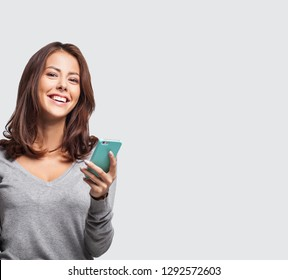 Young beautiful happy woman using smart phone. Isolated on grey background