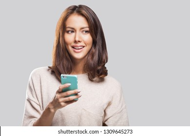 Young beautiful happy woman using smart phone. Isolated on gray background