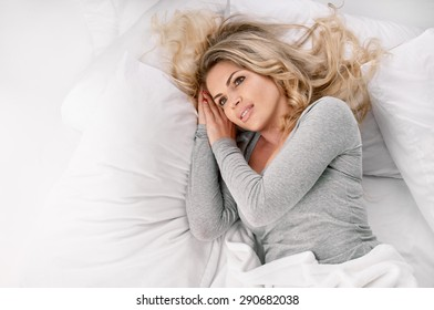 Young beautiful happy woman waking up on bed